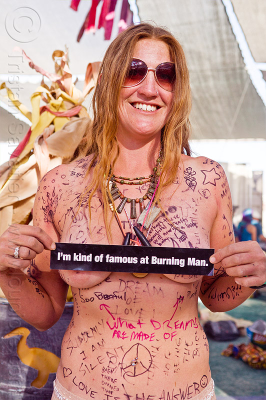 human graffiti wall - burning man 2012, body graffiti, bumper sticker, burning man, center camp, famous burner, graffiti wall, necklaces, skin graffiti, topless woman