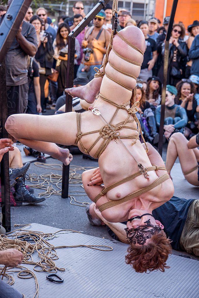 naked woman in upside down suspension bondage - folsom street fair 2015 (san francisco), carnival mask, chain, clamp, clover clamps, fetish, lace mask, masked, nude, rope bondage, suspension bondage, topless, upside down, woman