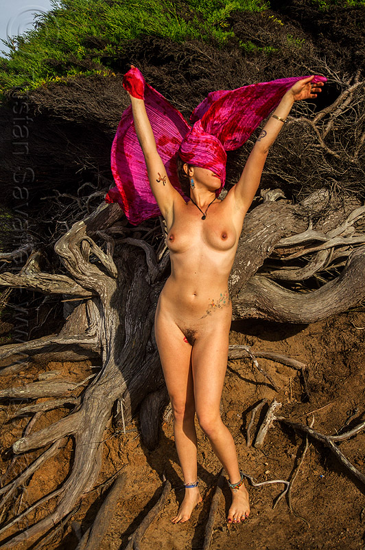 nude woman standing arms up with pink scarf covering face, ankle bracelets, anklets, arms up, breasts, juniper, naked, nude, pink scarf, roots, standing, tattoos, topless woman, tree, twisted