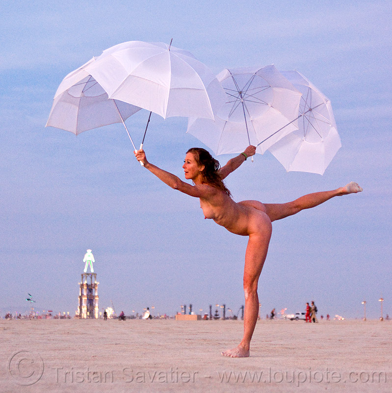 one of the women performing with the umbrella-man - burning man 2010, dawn, naked, nude, performance, the man, u-man, umbrella man, white umbrellas, woman