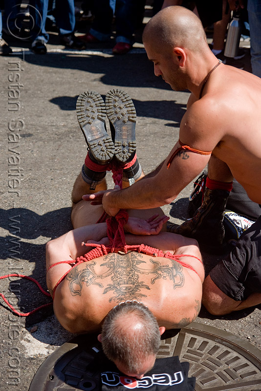rope bondage - tony buff tying-up derek da silva - dore alley fair (san francisco), back piece, derek da silva, dore alley fair, fetish, knots, men, red rope, rope bondage, tattooed, tattoos, tony buff