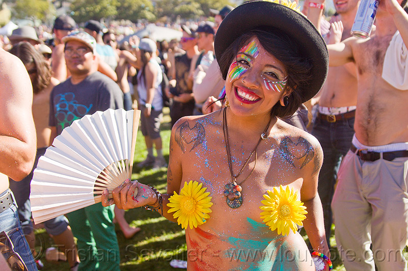 sunfower girl with face paint, hat and fan, black hat, face painting, facepaint, fan, gay pride festival, glitter, heart tattoos, josie, necklace, rainbow makeup, shoulder tattoos, sunflower pasties, sunflowers, winged hearts tattoos, woman, yellow flowers