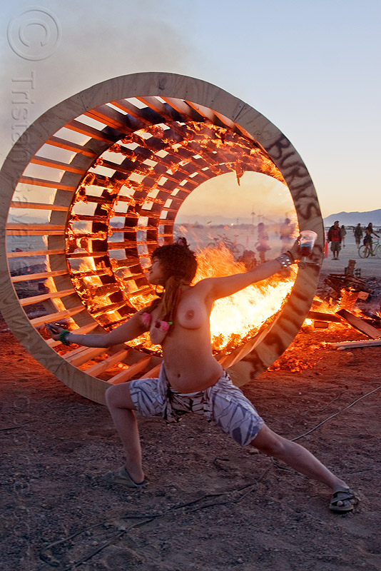 topless woman dancing at dusk in front of burning cylindrical wooden frame - burning man 2010, burning man, cylinder, cylindrical, dancing, dusk, fire, frame, heather, stretching, topless, woman, wood, wooden