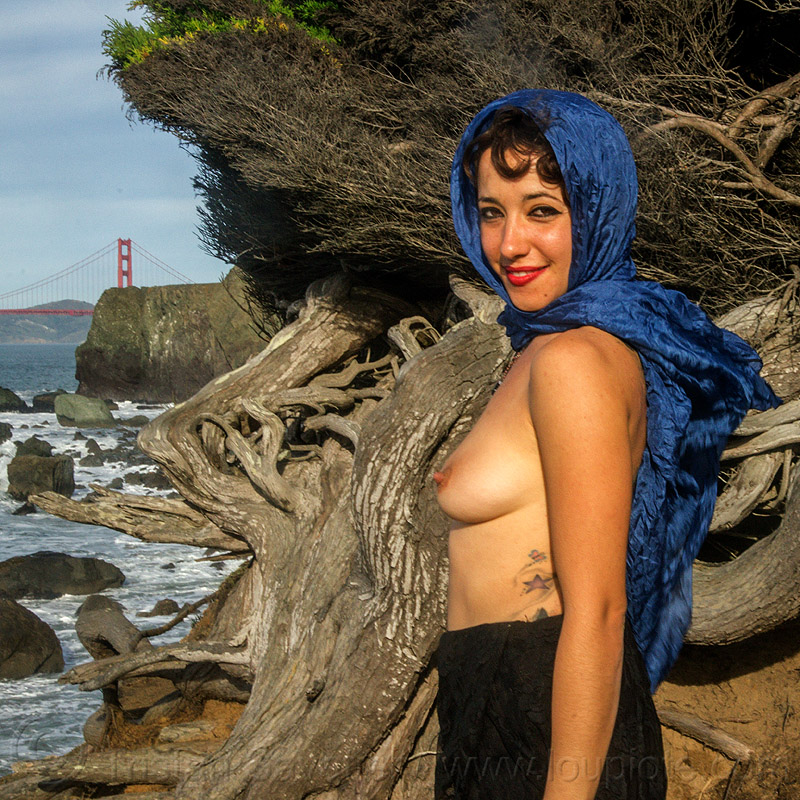 topless woman with blue scarf standing near juniper tree, blue scarf, breasts, cliff, fashion, golden gate bridge, ocean, rocks, roots, sea, seashore, shore, suspension bridge, topless woman, tree, twisted, water