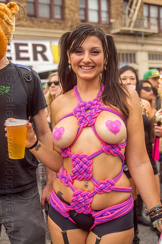 woman in pink and purple rope bondage costume, fetish, folsom street fair, japanese bondage, pasties, pink, purple, rope bondage, topless woman