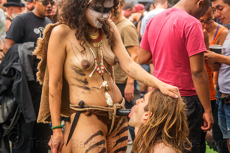 woman in tribal fetish costume and strap-on dildo getting blow job, blow job, body paint, body painting, costume, dildo harness, feathers, fetish, makeup, man, necklace, rope bondage, sex toy, strap on, topless, tribal, woman