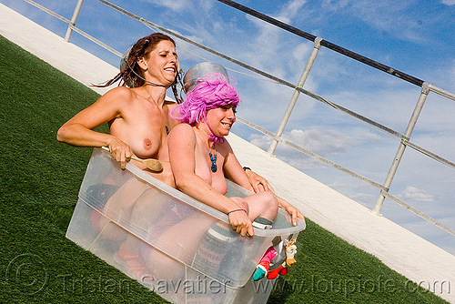 alissa and friend sliding fast on the wedge - burning man 2009, artificial turf, astroturf slide, burning man, girls, pink hair, pink wig, plastic box, sliding, synthetic turf, the wedge project, topless woman, women