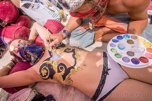 breasts bodypainting - burning man 2015, bandana, body art, bodypaint, bodypainting, burning man, center camp, justin stone, lying down, manon, painting, palette, topless woman