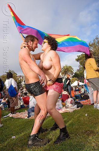 couple dancing with rainbow flag, dancing, flag pole, gay pride festival, man, rainbow flag, topless, woman