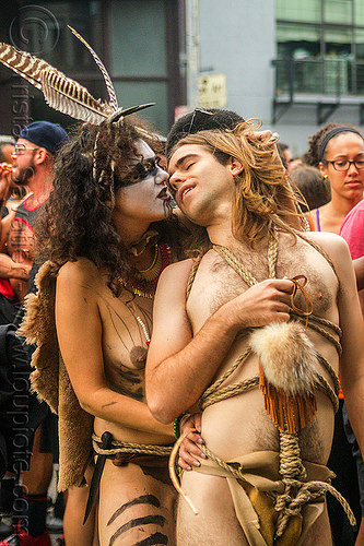 couple kissing - tribal fetish costume, body paint, body painting, costume, feathers, fetish, kissing, lovers, makeup, man, necklace, rope bondage, topless, tribal, woman