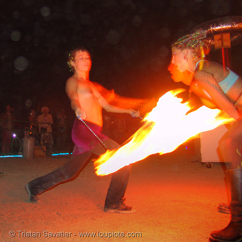 fire performers - decon and raine, burning man, fire dancer, fire dancing, fire performer, fire spinning, night, raine, shaina, spinning fire