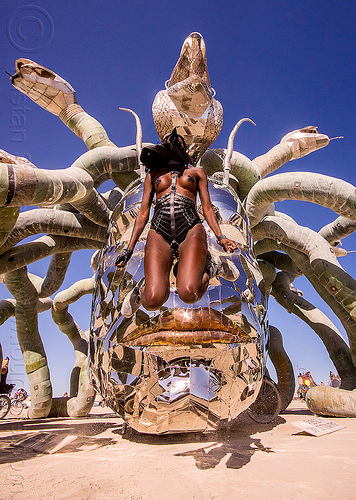 layla jumping in front of medusa - burning man 2015, art installation, head, jump, jumpshot, kevin clark, medusa madness, metal, sculpture, snakes, steel, woman