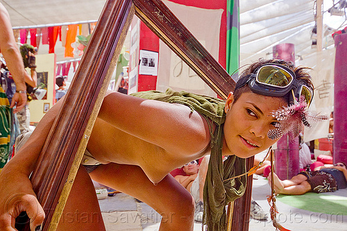 model in a picture frame - burning man 2012, burning man, center camp, feathers, goggles, green scarf, picture frame, topless woman, wooden frame