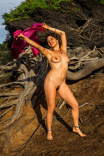 nude woman standing arms up holding pink scarf, ankle bracelets, anklets, arms up, juniper, nude, pink scarf, roots, standing, tattoos, topless, tree, twisted, woman