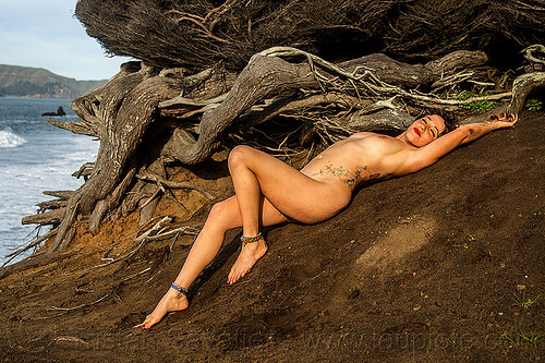 nude woman with tattoos lying down near juniper tree, ankle bracelets, anklets, beach, butterflies tattos, juniper, lying down, nude, roots, sand, seashore, stretching, tattoos, topless, tree, twisted, woman