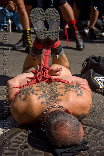 rope bondage - derek da silva tied-up by tony buff - dore alley fair (san francisco), back piece, boots, derek da silva, dore alley fair, fetish, knots, man, red rope, rope bondage, soles, tattooed, tattoos, tony buff