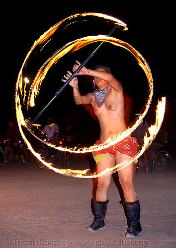 shireen spinning a fire staff - burning man 2007, breasts, circle, fire dancer, fire dancing, fire performer, fire spinning, fire staff, flames, long exposure, night, ring, shireen, spinning fire, topless woman