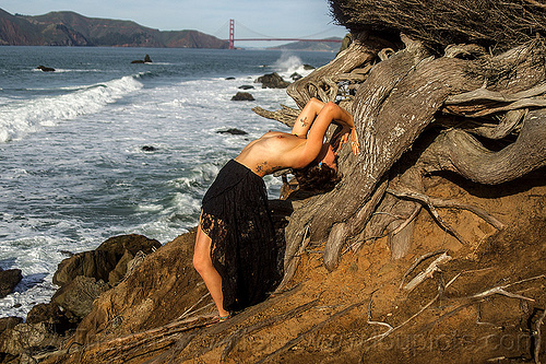 topless woman bending backward in yoga exercise on ocean rugged coast - twisted juniper tree, arched, bending backward, cost, golden gate bridge, juniper, rocks, roots, rugged, seashore, surf, suspension bridge, topless, tree, twisted, white water, woman, yoga