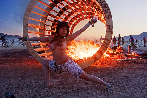 DSC07703 - burning man 2010 - topless woman dancing at dusk in front of burning cylindrical wooden frame, burning man, cylinder, cylindrical, dancing, dusk, fire, flames, frame, heather, stretching, topless woman, wood, wooden