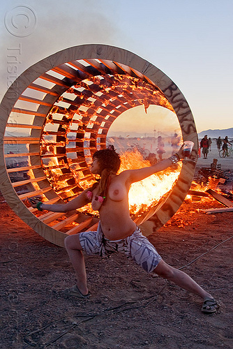 DSC07701 - burning man 2010 - topless woman dancing at dusk in front of burning cylindrical wooden frame, burning man, cylinder, cylindrical, dancing, dusk, fire, flames, frame, heather, stretching, topless woman, wood, wooden