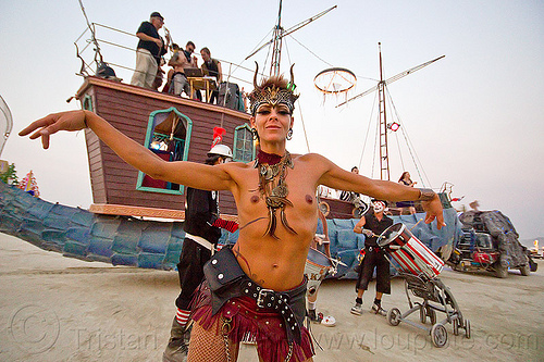 topless woman dancing - burning man 2013, burning man, dancing, fishyboat art car, headdress, marching band, mutant vehicles, narwhal art car, necklaces, topless, woman