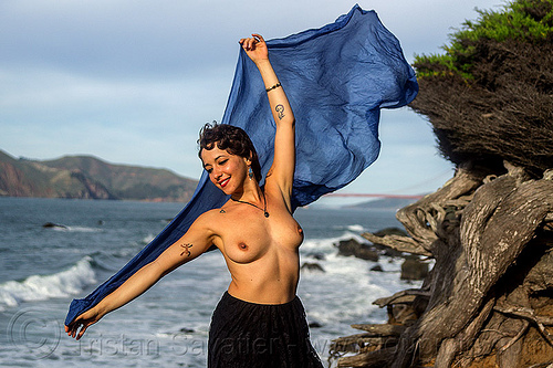 topless woman holding blue scarf in the wind on seashore, blue scarf, fashion, juniper, seashore, tattoos, topless, tree, wind, windy, woman
