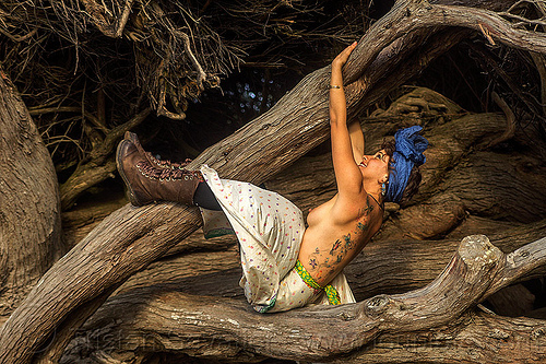 topless woman playing in old juniper tree, back tattoo, boots, breasts, butterflies tattoo, climbing, headband, headdress, holding, juniper, tattoos, topless woman, tree, trunk, white dress