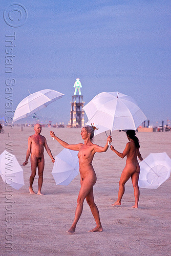 the umbrella-man performing at dawn - burning man 2010, burning man, dawn, naked, nude, performance, the man, u-man, umbrella man, white umbrellas, women