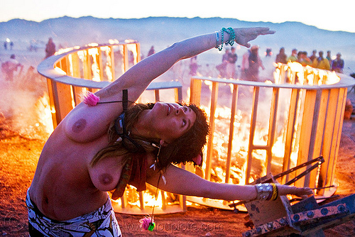 woman dancing in front of burning structure - heather, burning man, dawn, fire, flames, heather, stretching, topless woman, wood