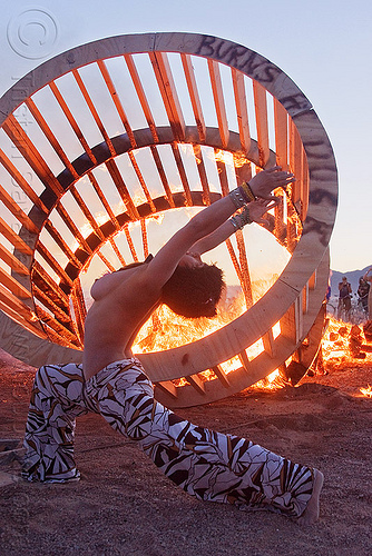 DSC07722 - woman dancing near fire, burning man, cylinder, cylindrical, dancing, dusk, fire, flames, frame, heather, stretching, topless woman, wood, wooden