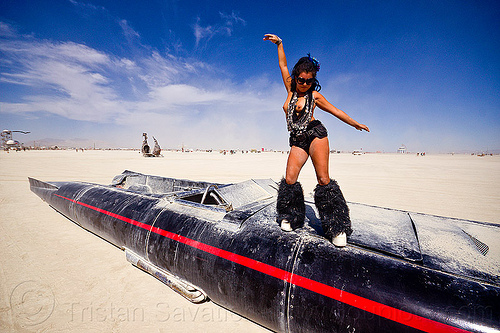 woman dancing on david best's rocket car - burning man 2012, art car, black leg warmers, burning man, dancing, furry leg warmers, long, mutant vehicles, necklaces, rocket car, topless, woman
