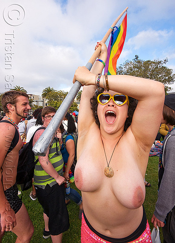 woman dancing with rainbow flag, breasts, dolores park, flag pole, gay pride festival, rainbow flag, sunglasses, topless woman