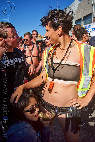 woman getting a dildo blow job - rayray - dore alley fair (san francisco), blow job, bondage, dildo harness, event staff, fetish, high-visibility jacket, high-visibility vest, man, rayray, reflective jacket, reflective vest, safety jacket, security, sex toy, strap on, woman