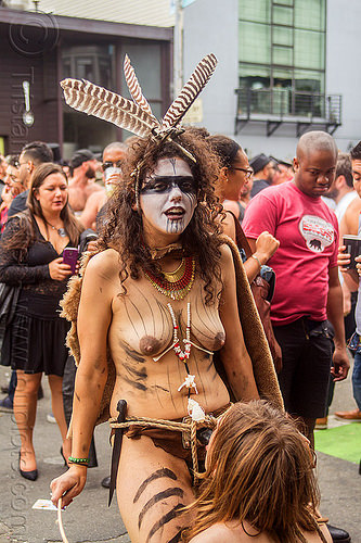 woman in tribal fetish costume, blow job, body paint, body painting, costume, dildo harness, feathers, fetish, makeup, man, necklace, rope bondage, sex toy, strap on, topless, tribal, woman