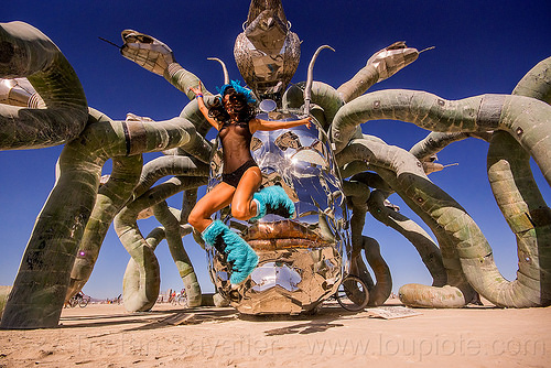 woman jumping in front of medusa madness - burning man 2015, anna kiss, art installation, head, jump, jumpshot, kevin clark, medusa madness, metal, sculpture, snakes, steel, woman