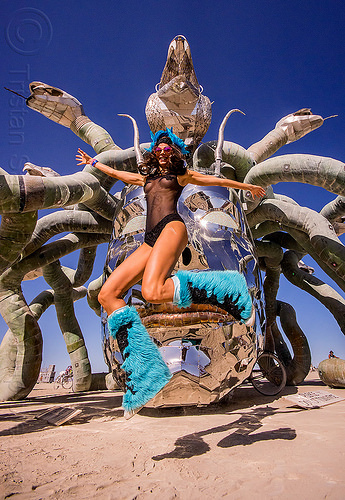 woman jumping in front of medusa madness - burning man 2015, anna kiss, art installation, burning man, head, jump, jumpshot, kevin clark, medusa madness, metal, sculpture, snakes, steel, woman