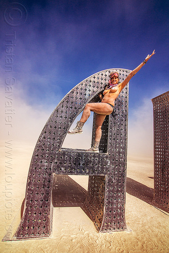 woman on @EARTH #HOME - giant letter sculpture - burning man 2016, @earth #home, art installation, big words, burning man, metal sculpture, steel, woman
