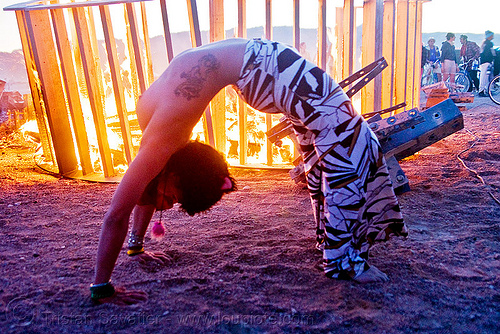 woman stretching near burning structure - heather, burning man, dawn, fire, flame, heather, stretching, tattooed, tattoos, topless woman, wood