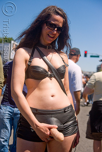 woman wearing leather harness and dildo - dore alley fair (san francisco), bondage, dildo harness, fetish, leather harness, sex toy, strap on, woman