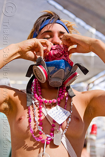 woman wearing pink and blue, bandana, breasts, burning man, center camp, dog tag, dust mask, headband, melissa, msa respirator, necklaces, topless woman