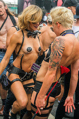 women dancing - leather fetish attire, arm tattoo, blonde, dancing, folsom street fair, pasties, topless woman, whip