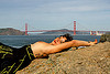 topless woman in black dress sunbathing near golden gate bridge, black dress, breasts, golden gate bridge, lying down, ocean, sea, seashore, shore, sunbathing, suspension bridge, topless woman, water