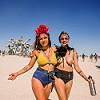 two girls in front of medusa - burning man 2015, arm tattoo, black feathers, burning man, chains, headdress, moth tattoo, om tattoo, sunglasses, topless woman, women