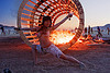 topless woman dancing at dusk in front of burning cylindrical wooden frame - burning man 2010, burning man, cylinder, cylindrical, dancing, dusk, fire, flames, frame, heather, stretching, topless woman, wood, wooden