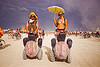 couple on segways - burning man 2012, burning man, clouds, couple, segway x2, segways, stormy sky, topless woman, umbrella